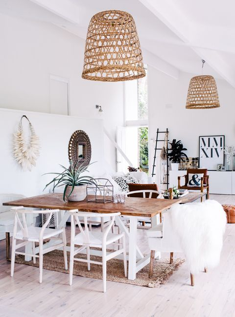 light and airy dining room with rustic boho feel. White chairs .
