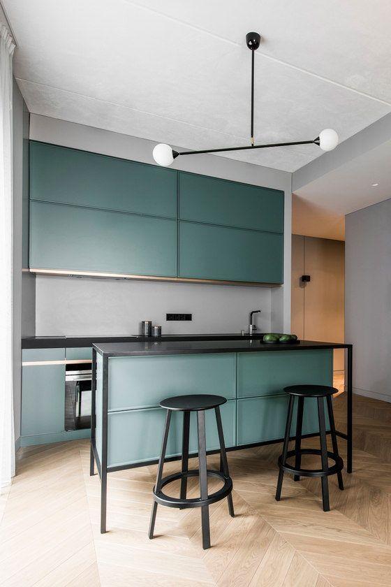 The kitchen features sleek green cabinets, a grey backsplash, a .