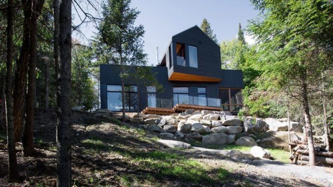 Black Quebec chalet by Atelier Boom-Town overlooks forest and lake .