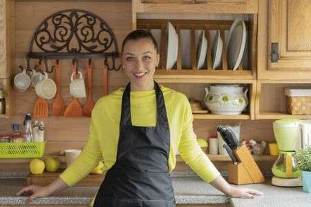 Beautiful Young Girl In Black Apron Poses In Kitchen Of Cozy .