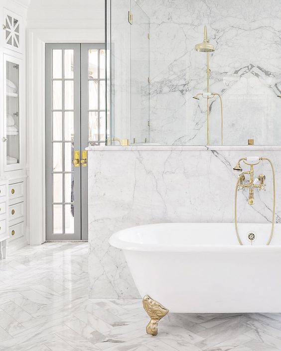 Choose marble walls and floors for your white bathroom to create a .