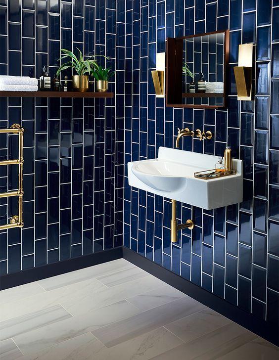 glossy navy tiles clad vertically for a bold art deco bathroom .