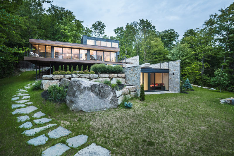 Wood And Stone Cover The Exterior Of This Multi-Level Modern House .