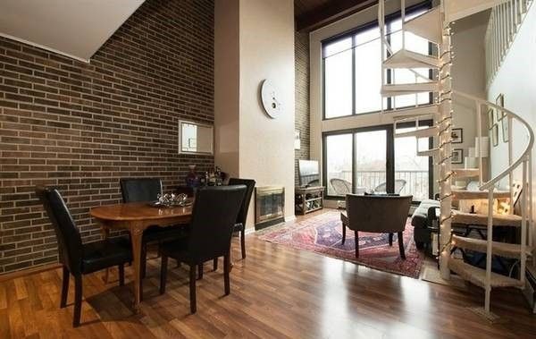 Contemporary loft apartment with exposed brick, wood burning .