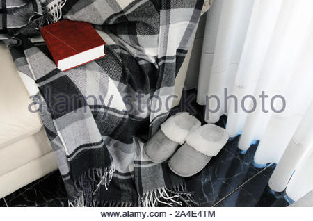 Woolen warm blanket and red book on white leather armchair, cozy .