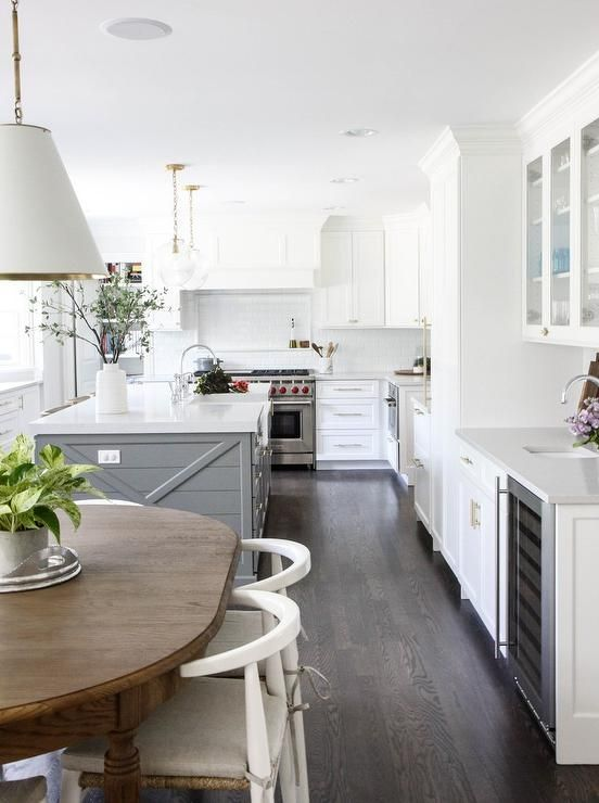 U-shaped white and gray kitchen boasts dark stained oak floor .