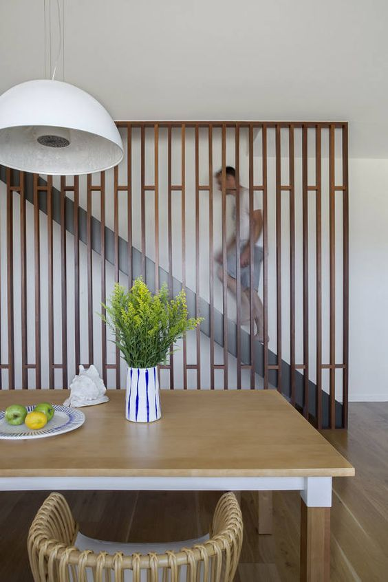 modern wooden screen to cover the staircase and make the dining .