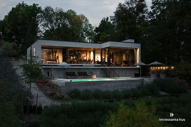 Contemporary lake house of concrete with a swimming pool .