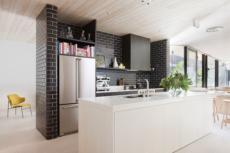 A central wall of glazed bricks forms the kitchen in this .