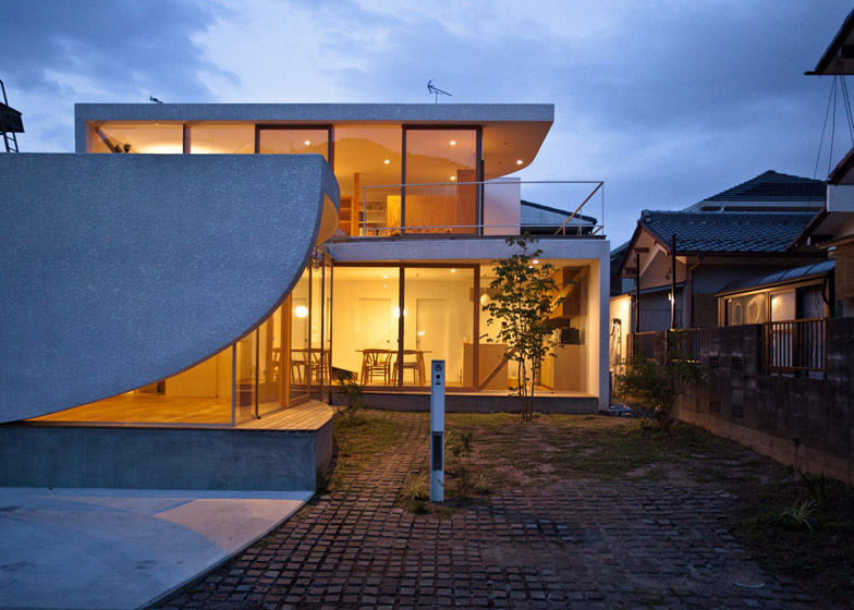 Curving walls eclipse the glazed facade of a Japanese hou