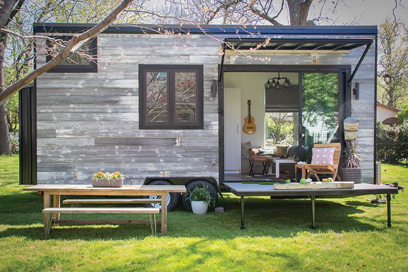 Tiny House — weathered wood exterior, built on a trailer platform .