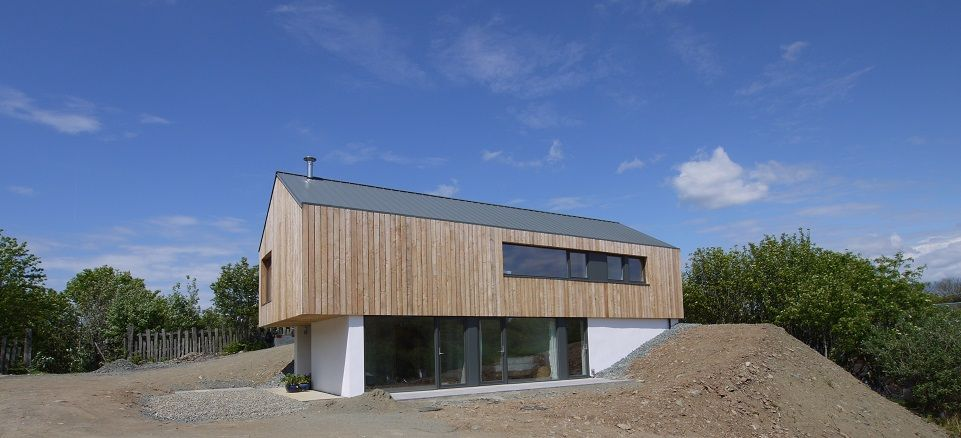 Vertical larch cladding on the upper floor and white render on the .