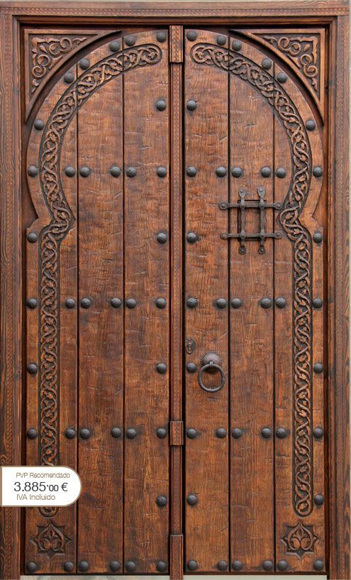 Beautiful wooden entrance door with engraving and iron studs .