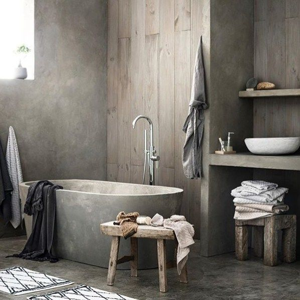 A bathroom with raw materials, like concrete and woodpanels, goes .