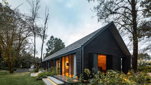 A Long and Narrow Cabin House With A Beautiful Burnt Wood Exterior .