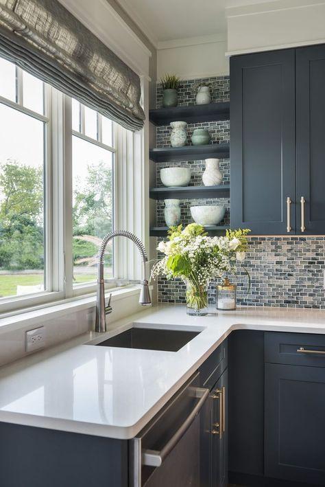 The glass mosaic backsplash in shades of swirled blues and grays .
