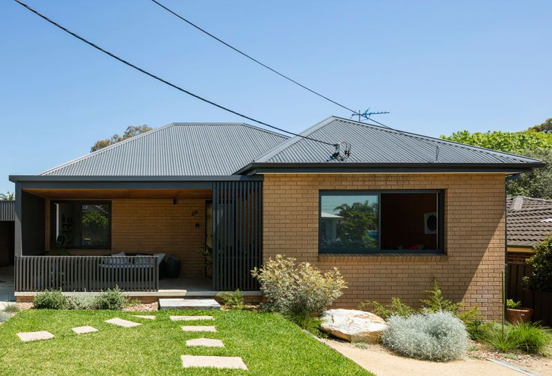 A Black Rear Extension Was Added To A 1960's Brick House In Sydney .