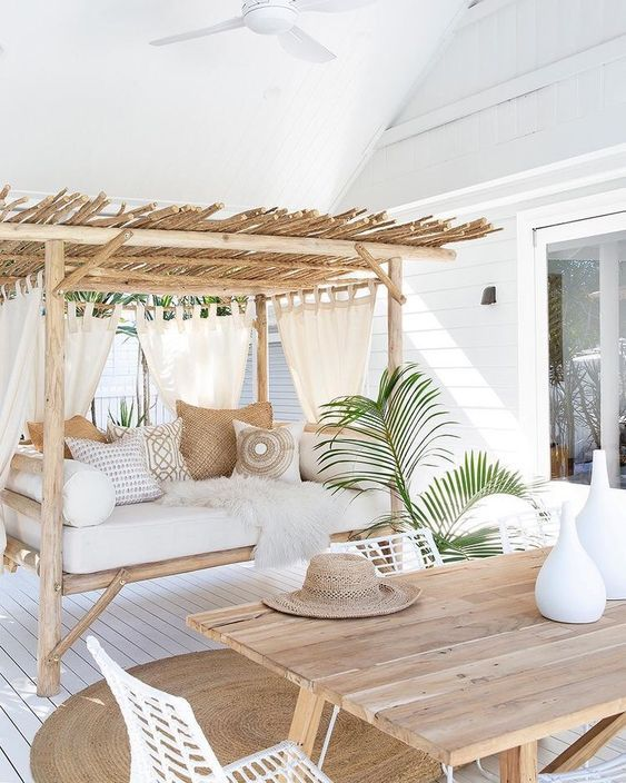 a welcoming tropical terrace with a wooden table, white metal .
