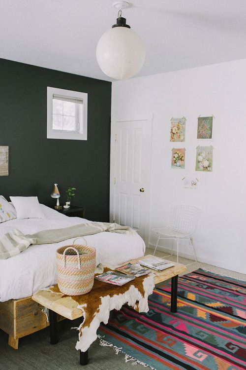 dark forest green wall with neutral bedding and natural accents .
