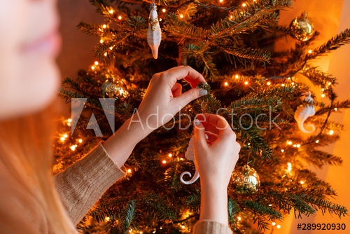 Happy young woman decorating christmas tree at home. Winter .