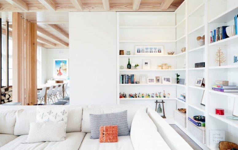 A Sofa With Cushions Placed Near A Big White Bookshelf With Many .