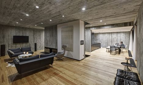 Timber-clad seaside house with wood-textured concrete interior by .